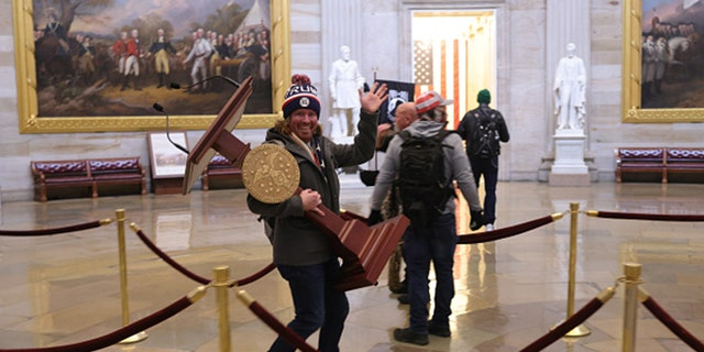 The man seen carrying the U.S. House lectern has reportedly been identified on social media. (Photo by Win McNamee/Getty Images)