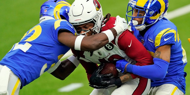 Arizona Cardinals wide receiver DeAndre Hopkins, center, is tackled by Los Angeles Rams strong safety Jordan Fuller, left, and cornerback Troy Hill during the first half of an NFL football game Sunday, Jan. 3, 2021, in Inglewood, Calif. (AP Photo/Ashley Landis)