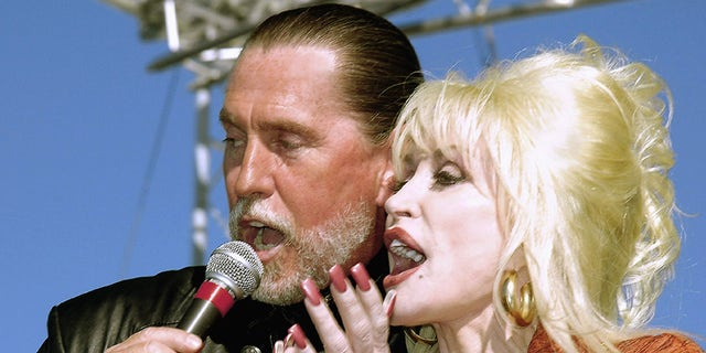 Dolly Parton shares the microphone with brother Randy Parton in Roanoke Rapids, N.C. in 2005.