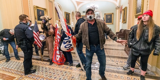 Supporters of President Trump are confronted by U.S. Capitol Police officers outside the Senate Chamber inside the Capitol, Wednesday, Jan. 6, 2021 in Washington.