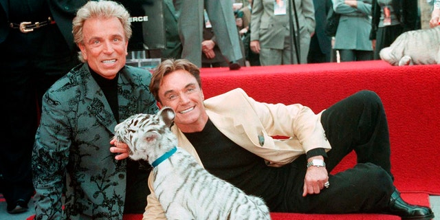 FILE - Illusionists Siegfried Fischbacher, left and Roy Uwe Ludwig Horn pose for photographers with a white tiger cub after they unveiled their star on the Hollywood Walk of Fame in Los Angeles, Calif.