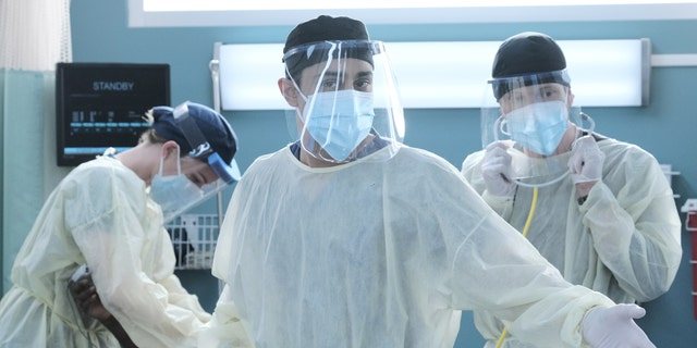 L-R: Emily VanCamp, Manish Dayal and Matt Czuchry in full PPE during the premiere episode of 'The Resident.'