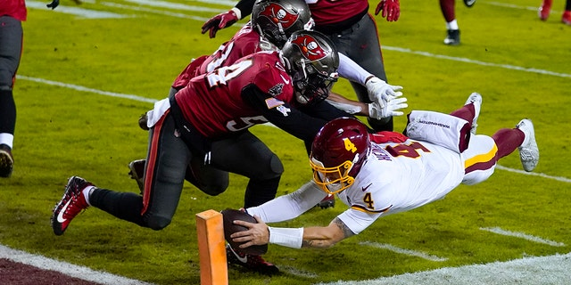 Washington Football Team quarterback Taylor Heinicke (4) dives to score a touchdown against Tampa Bay Buccaneers inside linebackers Kevin Minter (51) and Lavonte David (54) during the second half of an NFL wild-card playoff football game, sábado, ene. 9, 2021, in Landover, Maryland. (Foto AP / Julio Cortez)