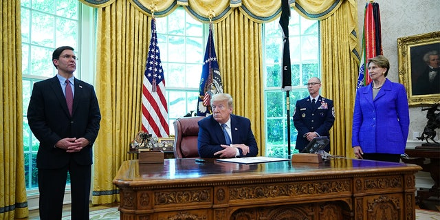 US President Donald Trump, with US Defense Secretary Mark Esper (L), Secretary of the Air Force Barbara Barrett (R) and US Space Force Senior Enlisted Advisor CMSgt Roger Towberman, attend presentation of the US Space Force Flag and the signing of Armed Forces Day Proclamation on May 15, 2020, in the Oval Office of the White House in Washington, DC. (Photo by MANDEL NGAN / AFP) (Photo by MANDEL NGAN/AFP via Getty Images)