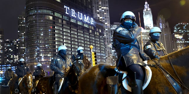 Police keep watch as a small group of demonstrators protest near Trump Tower on January 07, 2021 in Chicago, Illinois. (Photo by Scott Olson/Getty Images)