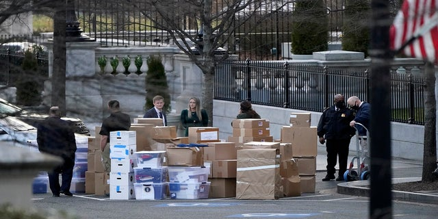 People wait for a moving van after boxes were moved out of the Eisenhower Executive Office building inside the White House complex on Thursday. (AP)