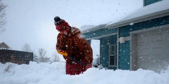 Tim Ahlman shovels snow outside his home in Bellemont, Ariz. on Monday. (AP)