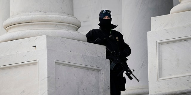 An armed U.S. Capitol Police officer looks out from the East side of the Capitol, during a rehearsal for President-elect Joe Biden's inauguration ceremony, at the Capitol in Washington, Maandag, Jan.. 18, 2021. (Associated Press)