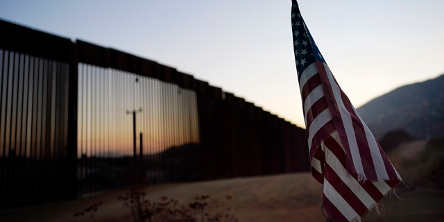 FILE - In this image submitted on September 24, 2020, the flag sits north of a section of the new border structure near Tecate, California.  The Trump administration tried to prevent immigrants from crossing the southwest border with measures that included forcing asylum seekers to do so in Mexico or Central America and build about 450 miles of walls.  .  (AP photo / Gregory bull)