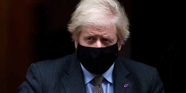 Johnson leaves 10 Downing Street for the House of Commons for the weekly Prime Ministers Questions in London, 星期三, 一月. 27, 2021. (AP Photo/Alastair Grant)