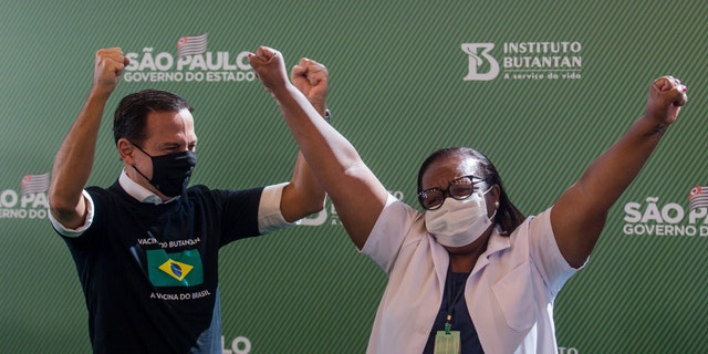 Nurse Monica Calazans, 54, and the Governor of Sao Paulo Joao Doria celebrate after she got her shot of the COVID-19 vaccine produced by China's Sinovac Biotech Ltd, at the Hospital das Clinicas in Sao Paulo, Brazil, Sunday, Jan. 17, 2021.