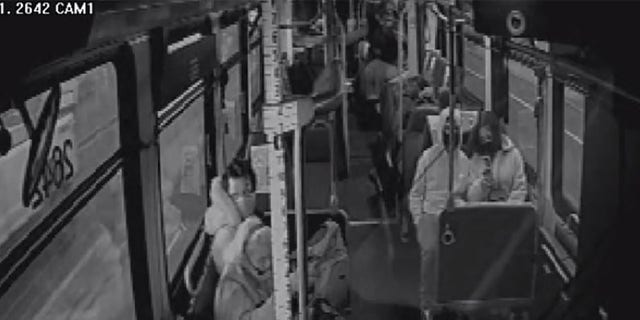 This still image taken from surveillance video aboard a Metro bus shows a man kicking a woman in the side of her head.