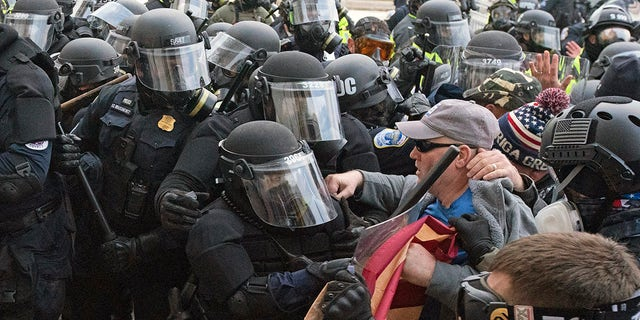 Capitol police officers in riot gear push back demonstrators who try to break a door of the U.S. Capitol on Wednesday, Jan. 6, 2021, in Washington. (AP Photo/Jose Luis Magana)
