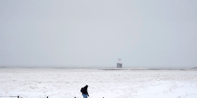 A lone man walks along a frozen section of North Ave. beach on Lake Michigan north of downtown Chicago on Tuesday. (AP)