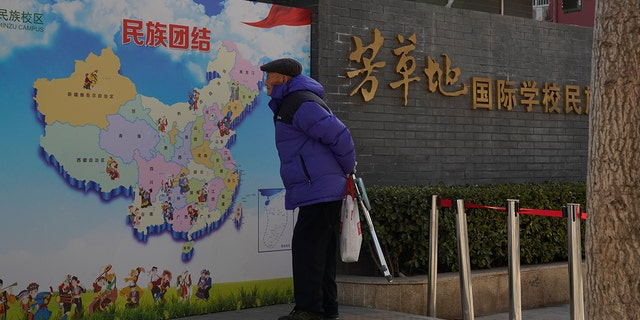 """An elderly Chinese man looks at map of Chinese showing its different ethnic groups and the slogan """"Ethnic Unity"""" a Pechino, China Monday, Jan. 11. (AP Photo/Ng Han Guan)"""