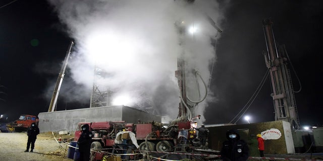 Chinese state media say 12 uit 22 workers trapped for a week by an explosion in the gold mine are alive, as hundreds of rescuers seek to bring them to safety. (AP/Xinhua)