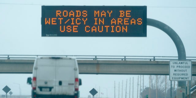 An electronic road sign warns motorists driving east on Interstate 70 about difficult driving conditions when a winter storm sweeps over the mountain west on Tuesday in Aurora, Colo.  (AP)