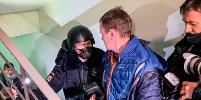 A police officer pushes photographers from a door of the apartment where Oleg Navalny, brother of jailed opposition leader Alexei Navalny lives in Moscow, 러시아, 수요일, 1 월. 27, 2021. Police are searching the Moscow apartment of jailed Russian opposition leader Alexei Navalny, another apartment where his wife is living and two offices of his anti-corruption organization. Navalny's aides reported the Wednesday raids on social media. (AP Photo/Mstyslav Chernov)