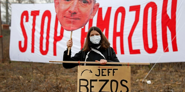 """OURNES, FRANCE - 일월 30: An opponent holds a cutout sign depicting Amazon CEO Jeff Bezos, in front of a banner reading """"Stop Amazon"""" during a rally against plans to build a giant Amazon warehouse on January 30, 2021 in Fournes (Gard), 프랑스. The project to set up a huge Amazon warehouse by the e-commerce giant in Fournes, near the Pont du Gard, faces strong opposition. The demonstrators oppose the """"betonization"""" 의 14 hectares of land a few kilometers from the Pont du Gard, (classified as a historical monument as a UNESCO World Heritage Site). (Photo by Chesnot/Getty Images)"""