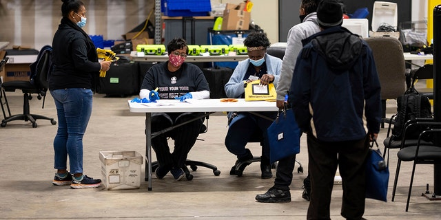 Elections workers at the Fulton County Georgia elections warehouse check in voting machine memory cards that store ballots following the Senate runoff election in Atlanta on Tuesday, Jan. 5, 2021. (AP Photo/Ben Gray)