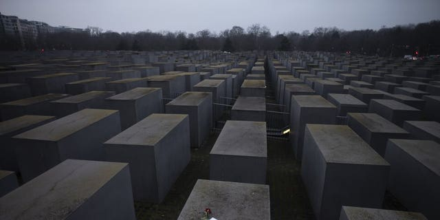 """Roses with a note that says """"#we remember"""", placed on the Holocaust Memorial on International Holocaust Remembrance Day in Berlin, Germany, Wednesday, January 27, 2021. (AP Photo / Markus Schreiber)"""