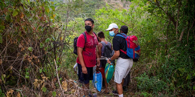 Honduran migrants observe a police checkpoint as they take an alternative route to avoid being detained in Chiquimula, Guatemala, Tuesday, Jan. 19, 2021. (AP Photo/Oliver de Ros)
