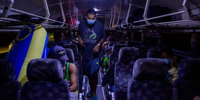 Honduran migrants wait inside a bus to be returned to San Pedro Sula near El Florido, Honduras, a border point between Guatemala and Honduras, Tuesday, Jan. 19, 2021. (AP Photo/Oliver de Ros)