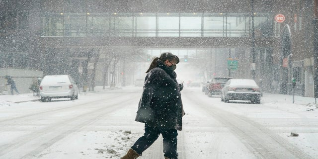 A pedestrian crosses a snow covered street on Monday in downtown Des Moines, Iowa. (AP)