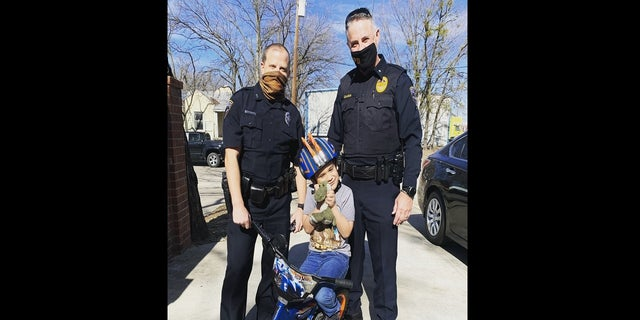 Detective Josh Smith, left, helped present a new bicycle to the child after his was destroyed. (Irving Police Department)
