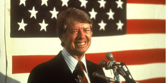 U.S. president Jimmy Carter smiling at a podium in front of an American flag, 1970s. (Photo by Hulton Archive/Getty Images)
