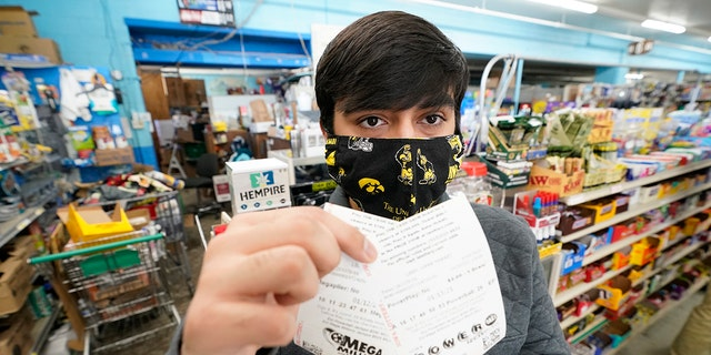 Hardik Kalra, of Des Moines, Iowa, poses for a photo with his Mega Millions and Powerball lottery tickets on Tuesday, Jan.12, 2021, in Des Moines, Iowa.  Lottery players stand a chance of hitting the biggest jackpots in nearly two years as Tuesday's Mega Millions rose to around $ 625 million and Wednesday's Powerball to $ 550 million.  (AP Photo / Charlie Neibergall)