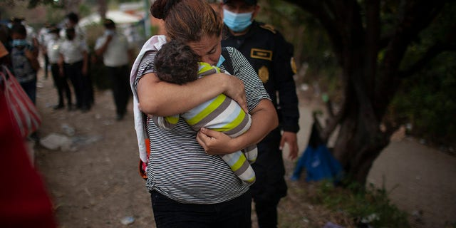 A woman carries her son as Honduran migrants confront Guatemalan soldiers and police manning a roadblock that prevents them from advancing toward the US, on the highway in Vado Hondo, Guatemala, Monday, Jan. 18, 2021. (AP Photo/Sandra Sebastian)