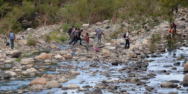 Honduran migrants walk away from clashes with Guatemalan soldiers and police blocking them from advancing toward the US, on the highway in Vado Hondo, Guatemala, Monday, Jan. 18, 2021. (AP Photo/Sandra Sebastian)