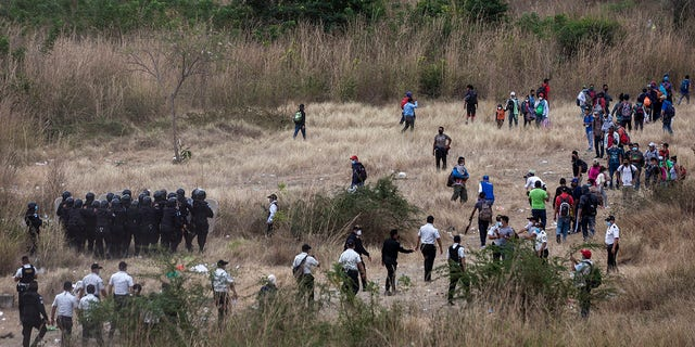 Honduran migrants, right, clash with Guatemalan soldiers and police who keep them from advancing toward the US border, on the side of the highway in Vado Hondo, Guatemala, Monday, Jan. 18, 2021. (AP Photo/Sandra Sebastian)