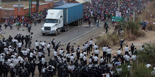 Honduran migrants, top, stand behind a cargo truck as they confront Guatemalan soldiers and police blocking them from advancing toward the US, on the highway in Vado Hondo, Guatemala, Monday, Jan. 18, 2021. (AP Photo/Sandra Sebastian)