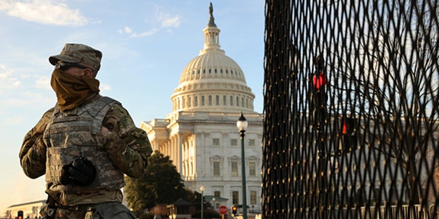 A member of the New York National Guard stands at a gate outside the U.S. Capitol the day after the House of Representatives voted to impeach President Trump for the second time Jan. 14, 2021 in Washington, D.C.