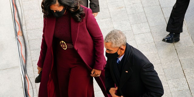 The former first lady wore a purple, almost burgundy overcoat by Black American designer Sergio Hudson for Wednesday's event, completed with a matching belt cinched at her waist with a gold circle buckle.