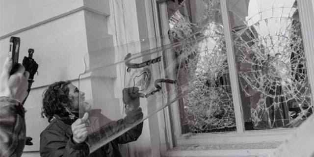 Pezzola seen using a stolen police riot shied to smash a window at the U.S. Capitol on Jan. 6. (Justice Department)