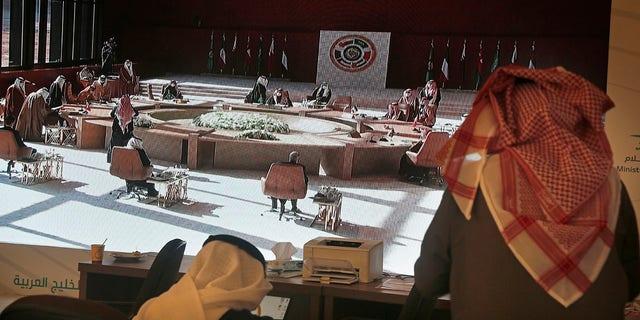 सऊदी के पत्रकार अल उला, सऊदी अरब में मंगलवार, 5 जनवरी, 2021 को होने वाली 41 वीं खाड़ी सहयोग परिषद (जीसीसी) की बैठक को दिखाते हुए एक स्क्रीन देखते हैं। कतर के सत्तारूढ़ अमीर अरब के उच्च-स्तरीय सम्मेलन में भाग लेने के लिए सऊदी अरब पहुंचे। एक घोषणा के बाद नेताओं ने कहा कि राज्य छोटे खाड़ी राज्य पर अपने वर्षों के प्रतिबंध को समाप्त कर देगा।  (एपी फोटो / अमृत नबील)