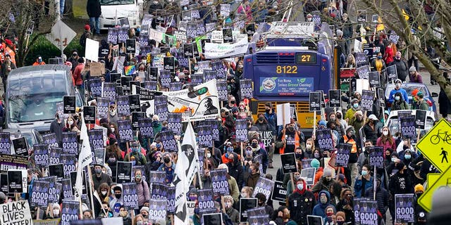 """Demonstrators fill a street and march around a bus stopped in the crowd during the 39th annual Seattle MLK Jr. Day March and Rally, Monday, Jan. 18, 2021, in Seattle. The event celebrates the national holiday in honor of the Rev. Martin Luther King Jr.'s birthday and this year's theme was """"Good trouble, necessary trouble,"""" in honor of the words of the late Congressman John Lewis. (AP Photo/Elaine Thompson)"""