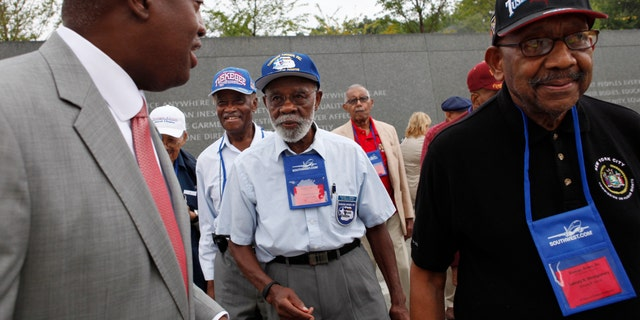FILE - In this Aug. 3, 2011, file photo, Harry E. Johnson Sr., left, president & CEO of the Martin Luther King Jr. Foundation, takes Tuskegee Airmen, including Theodore Lumpkin Jr., center, and Dabney Montgomery, right, on a tour of the Martin Luther King Jr. Memorial in Washington. Lumpkin has died from complications of the coronavirus, it was announced Friday, Jan. 8, 2021. Lumpkin was just days short of his 101st birthday. Lumpkin, a Los Angeles native, died Dec. 26, according to a statement from Los Angeles City College, which he attended from 1938 to 1940. (AP Photo/Jacquelyn Martin, File)