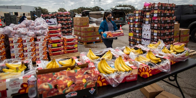 A volunteer carries food to be distributed during the Neighborhood Super Site food distribution event organized by the Houston Food Bank and HISD, Sunday, Feb. 21, 2021, in Houston. (Marie D. De Jesús/Houston Chronicle via AP)