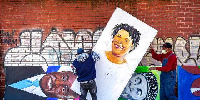 Artists set up a painting of Stacey Abrams in the King Historic District on Monday, Jan. 18, 2021, in honor of Martin Luther King Jr. Day, in Atlanta.