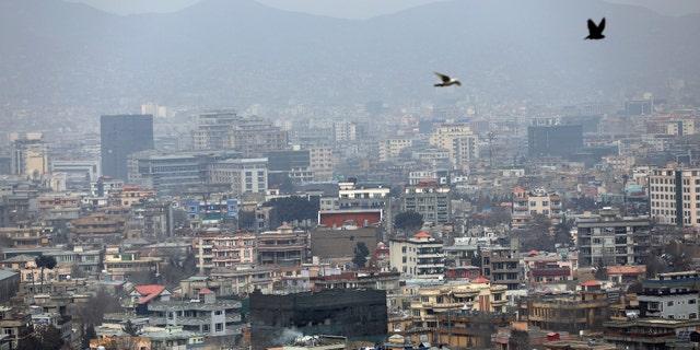 Birds fly over the city of Kabul, Afghanistan, Sunday, Jan. 31, 2021. (AP Photo/Rahmat Gul)
