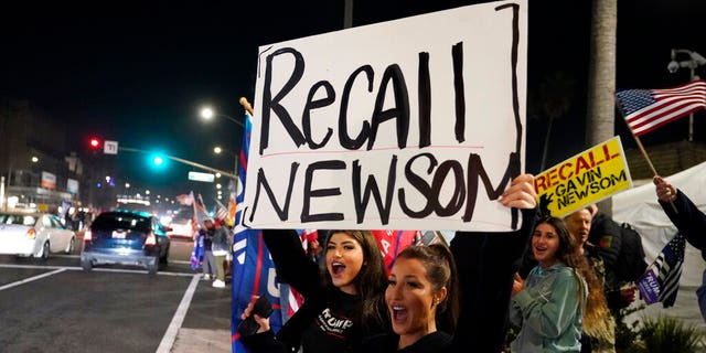 FILE: Demonstrators shout slogans while carrying a sign calling for the recall of Gov. Gavin Newsom during a protest against a stay-at-home order amid the COVID-19 pandemic in Huntington Beach, Calif.