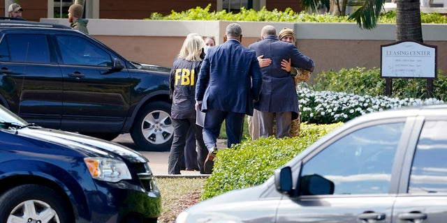 Law enforcement officers work where a shooting occurred wounded several FBI personnel while serving an arrest warrant, Tuesday, Feb. 2, 2021, in Sunrise, Fla. Police in South Florida have swarmed a neighborhood following a Tuesday morning shooting involving FBI agents. (AP Photo/Marta Lavandier)