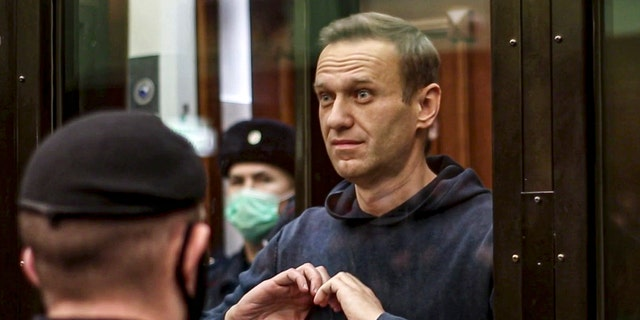 FILE - In this handout photo taken from a footage provided by Moscow City Court on Tuesday, Feb. 2, 2021, Russian opposition leader Alexei Navalny shows a heard symbol standing in the cage during a hearing to a motion from the Russian prison service to convert the suspended sentence of Navalny from the 2014 criminal conviction into a real prison term in the Moscow City Court in Moscow, Russia. A prison sentence for Navalny and a sweeping crackdown on protesters demanding his release reflect the Kremlin's steely determination to fend off threats to its political monopoly at any cost. (Moscow City Court via AP, File)