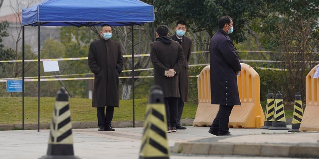 Security personnel watch a checkpoint into the cordoned off area where a World Health Organization team is staying at a hotel in central China's Hubei province on Thursday, Feb. 4, 2021. The WHO team is investigating the origins of the coronavirus pandemic in the province. (AP Photo/Ng Han Guan)