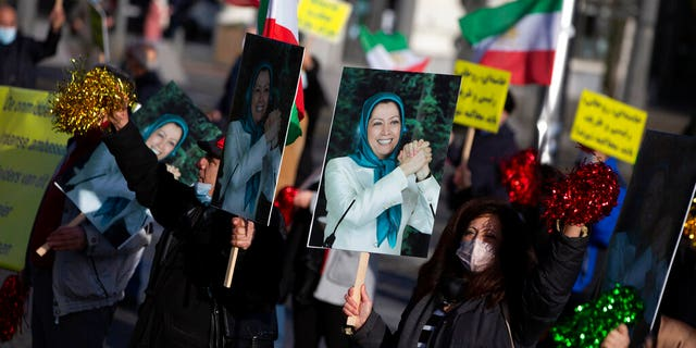 People demonstrate while holding photos of Maryam Rajavi, leader of the National Council of Resistance of Iran, during the trial of four persons, including an Iranian diplomate and Belgian-Iranian couple at the courthouse in Antwerp, Belgium, Thursday, Feb. 4, 2021. (AP Photo/Virginia Mayo)