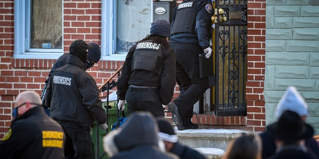 A Baltimore Police forensics team enters the house in West Baltimore where a U.S. Marshall was shot while serving an arrest warrant on Thursday, Feb. 4, 2021.  (Jerry Jackson/The Baltimore Sun via AP)